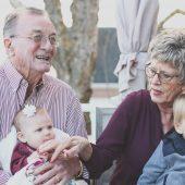 Avô e avó segurando duas crianças no colo